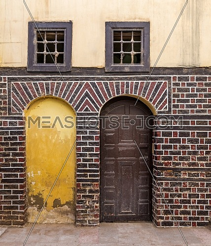 Stone blocked arced door, decorated wooden arched door, and two small windows with iron rusted bars on black and red bricks wall on cobblestone road