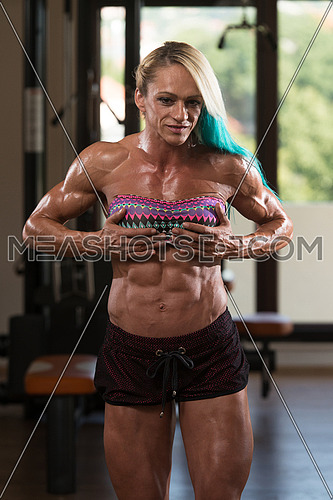 Portrait Of A Middle Aged Woman Posing Bodybuilding Poses In Modern Fitness Center