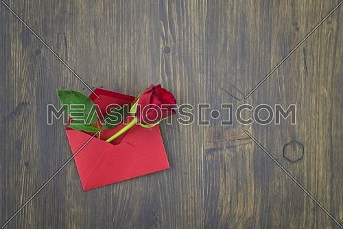Red rose in envelope on wooden background with free copy space. Wishes, greetings and love message