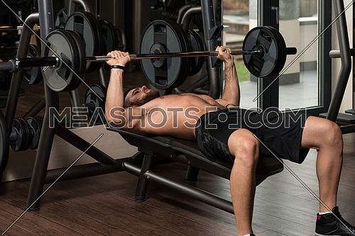 Handsome Man Is Working Out Chest With Barbell In A Modern Gym