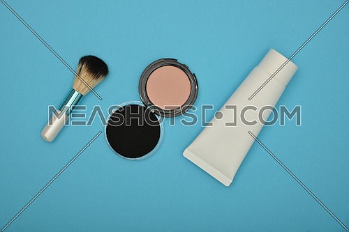Close up set of face makeup blush, beige sponge, foundation and brush over blue background, elevated top view, directly above