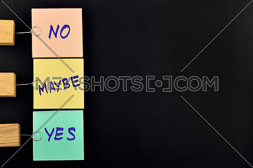 Yes, no, maybe, list, three paper notes, green, yellow, pink, with wooden holder isolated on black paper background for presentation