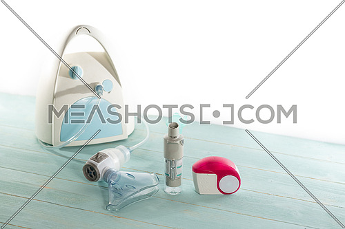 Set of asthma inhaler and aerosol machine with inhaler mask,concept asthma and treatment on green background,copy space.