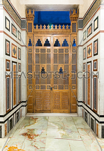 Ancient hand carved door, decorated colored marble wall, and white marble floor, Medieval Cairo, Egypt