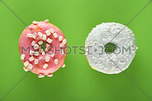 Two round ring donuts, one in blue glaze with white sprinkles topping decoration and pink with small marshmallows on green paper surface