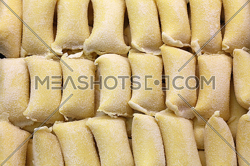 Fresh traditional homemade rustic artisan gourmet Italian ravioli stuffed pasta in retail display, close up, high angle view