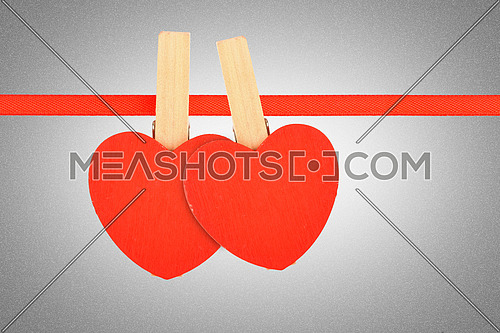 Valentine day template, two red wooden hearts with clothes pins on textile ribbon over grayscale grain noise gradient