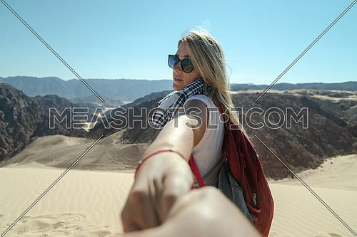 Follow me shot with blond female tourist in Ain Hodouda in sinai by day