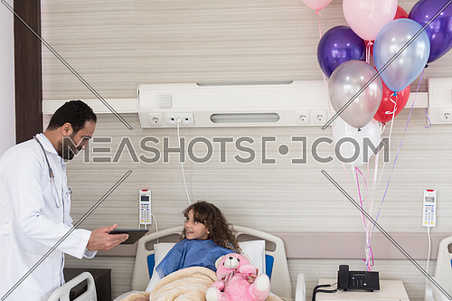 arabian mischievous and beauty kid get treatment by young doctor in modern hospital room