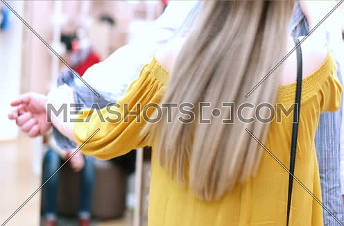 young man with woman choosing clothes in mall or clothing store