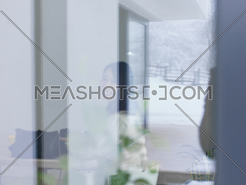 young beautiful asian woman sitting near window at cold winter day