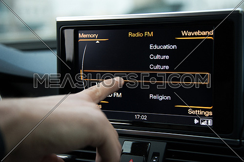 A man pressing on a digital pannel inside a car to control FM radio or mp3 player or cd player