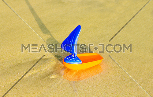a plastic toy boat on the beach