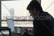 a man sitting beside a window working on laptop and listening to music