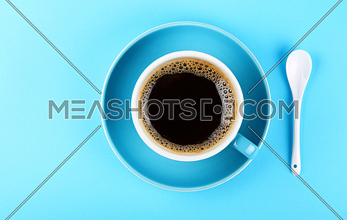 Close up one full cup of black Americano coffee and saucer with white spoon over pastel blue paper background, elevated top view, directly above