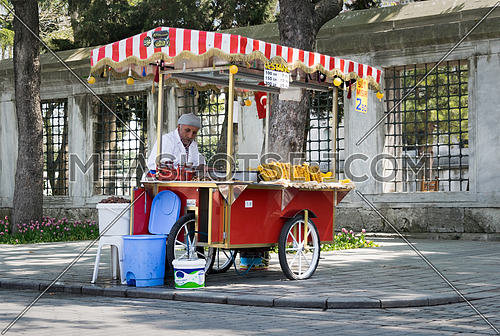 Istanbul, Turkey - April 16, 2017: Old man selling chestnut and corn on traditional Turkish fast food cart in Sultan Ahmed Square