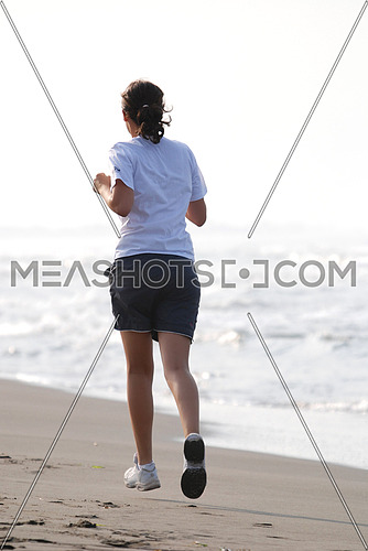 A young woman jogging by the sea