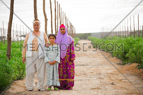 A farmer family posing to the camera in the farm