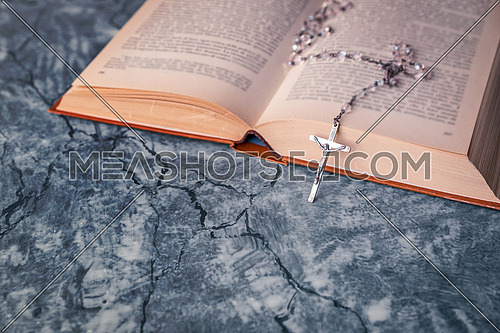 Silver rosary and cross with jesus on the Bible on a gray table. Religion at school.