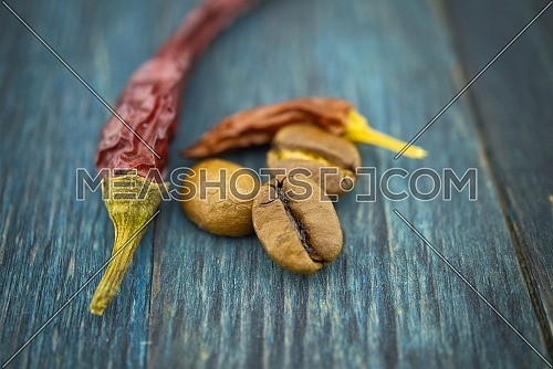 Dried red chili pepper and roasted coffee beans on wooden background. Macro photo
