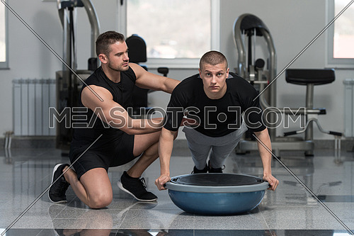 Personal Trainer Showing Young Man How To Train On Bosu Push Ups In A Health And Fitness Concept