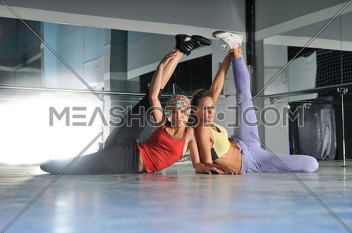 two womans work out and streaching legs in fitness club