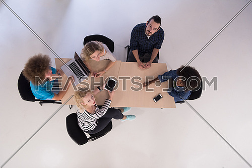 Multiethnic startup business team on meeting in modern bright office interior brainstorming, working on laptop and tablet computer top view