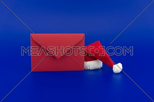 Red envelope for greetings and Santa hat on a festive blue background. New Year and Christmas greeting season concept