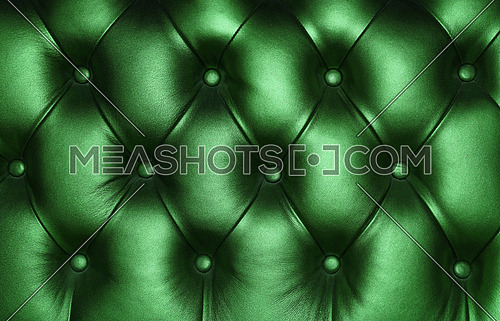 Dark emerald green capitone genuine leather background, retro Chesterfield style soft tufted furniture upholstery with deep diamond pattern and buttons, close up