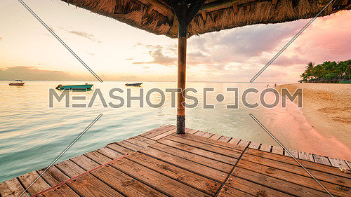 Perspective view of a wooden pier that create two amazing frame at sunset in Mauritus island