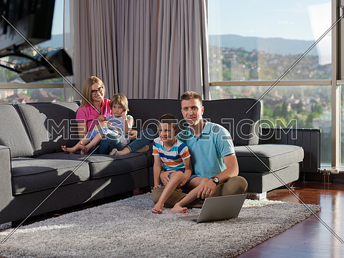 young happy family relaxing at home using laptop and tablet computers in luxury living room