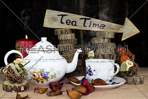 Cup of Tea and Teapot On Wooden Table. Arrow Sign With Text, Tea Time Written On It in The Background