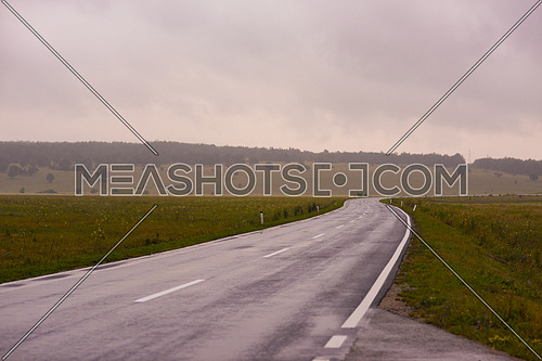 Long shot for asphalt road in beautiful nature showing a green hill in background at day.