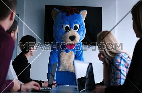 boss dressed as bear having fun with business people in trendy office