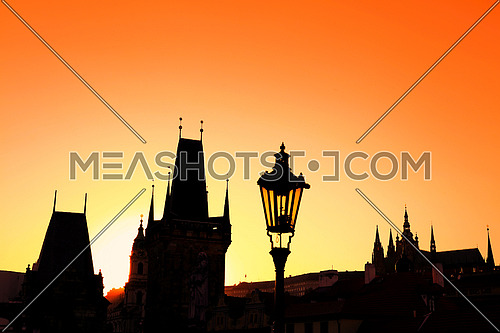 Sunset backlit silhouettes of street lamp post and roofs of cityscape skyline at Charles Bridge in Prague, Czech Republic