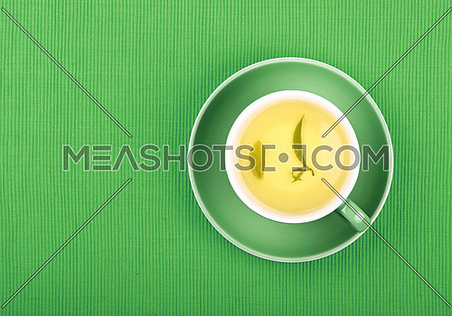 Full cup of clear green tea with floating leaves on saucer over green textile tablecloth, close up, elevated top view
