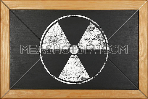 White chalk radioactive hazard warning sign over grunge black background of chalkboard with copy space