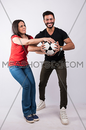 young couple standing and playing with a ball on white background