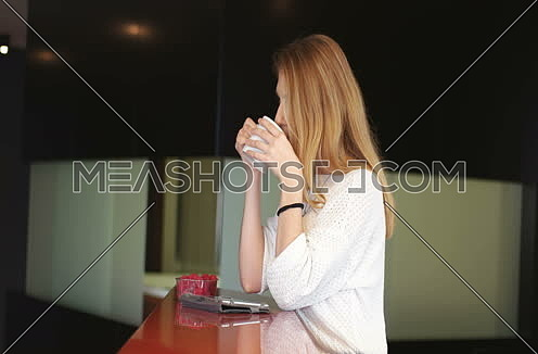 Blond Woman Using Mobile Phone At Home Drinking Coffee Enjoying Relaxing