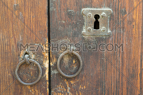 Two rusty iron ring door knobs and keyhole over an old wooden grunge door