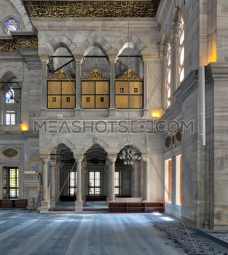 Interior of Nuruosmaniye Mosque, an Ottoman Baroque style mosque built in 1755, with arcades, wooden doors, windows, and blue carpet, located in Shemberlitash, Fatih, Istanbul, Turkey
