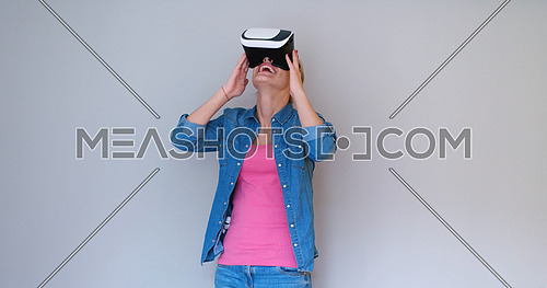Happy girl getting experience using VR headset glasses of virtual reality, isolated on white background