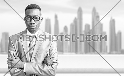 Portrait of young black businessman standing on balcony in front of the big city