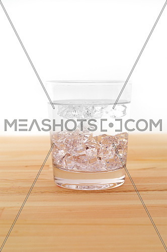 glass of pure ice water over a wood table white background