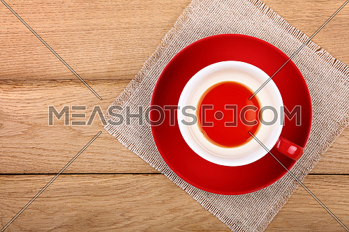 Empty finished cup of black tea on red porcelain saucer over wooden table with textile tablecloth napkin, close up, elevated top view, directly above