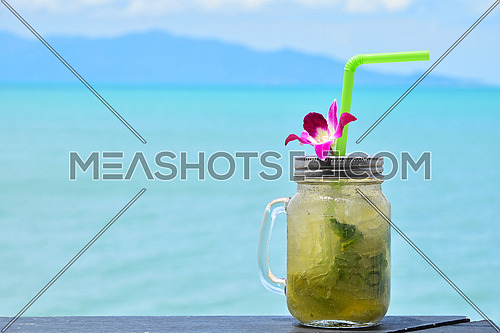 Big jars mug style full glass of fresh frozen mojito with metal cap lid, straw and purple orchid flower in cafe on the beach
