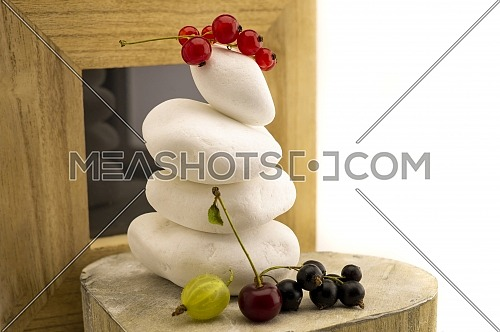 Stacked balancing white stones reflecting in a small mirror with fresh fruit including a gooseberry, red and black currants and a cherry in a healthy diet or spa still life in close up