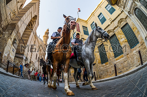 low angel for twoTourism and Antiquities Police riding horses in Al - Moez Street at day