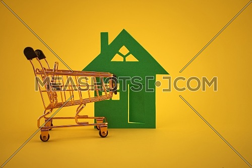 Buy real estate concept with house and shopping cart over yellow background and free copy space for text