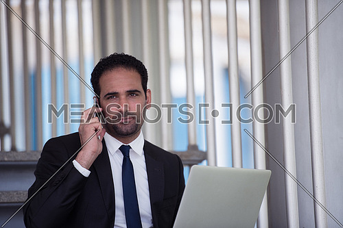 Young middle eastern business executive sitting on the stairs of a corporate office working with his laptop and talking on the phone